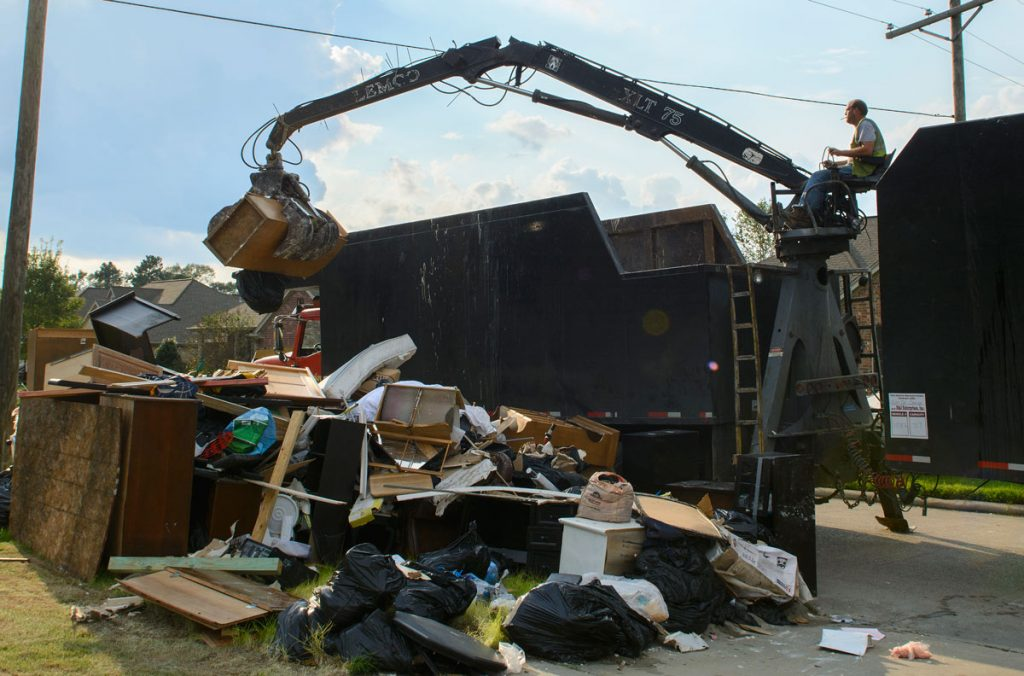 A FEMA employee scoops up soaked and water-damaged debris from Willis' neighbor's yard to carry away in a dump truck. Photo by Marlee Crawford