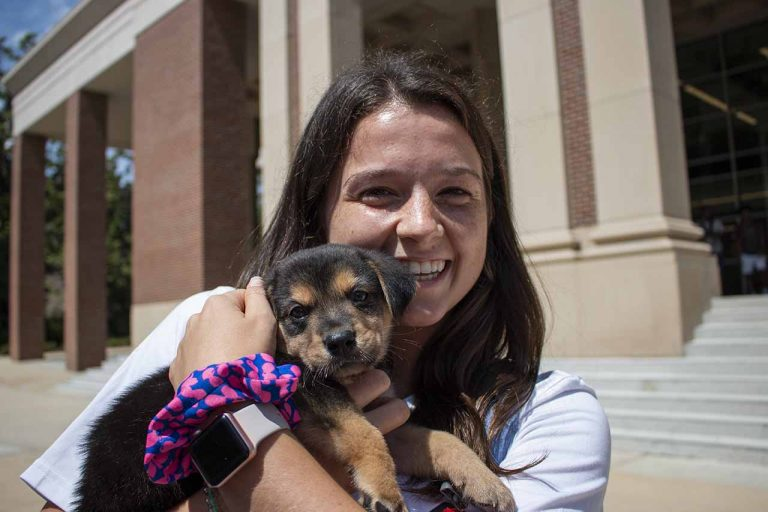 Brianna Berry holds a puppy outside the student union as part of the Welcome Week festivities. Welcome Week events are hosted by the Student Activities Association. Photo by Billy Schuerman.
